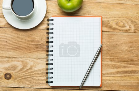 Photo for White blank notepad with cup of coffee , green apple and pen on wooden table - Royalty Free Image