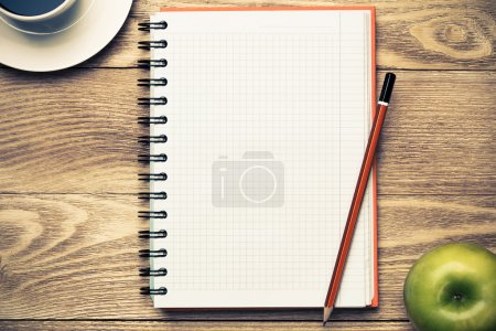 Photo for White blank notepad with cup of coffee,green apple and pencil  on wooden table - Royalty Free Image