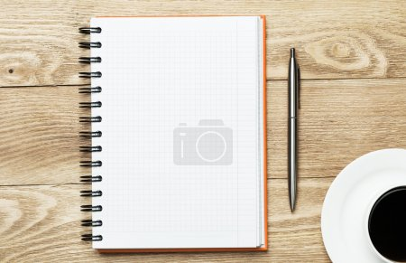 Photo for White blank notepad with cup of coffee and pen on wooden table - Royalty Free Image