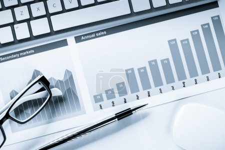 Photo pour Lieu de travail d'affaires avec clavier, souris d'ordinateur et papiers avec graphiques et diagrammes - image libre de droit