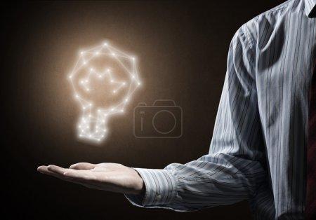 Photo pour Gros plan de main d'homme d'affaires tenant incandescent ampoule signe dans paume - image libre de droit