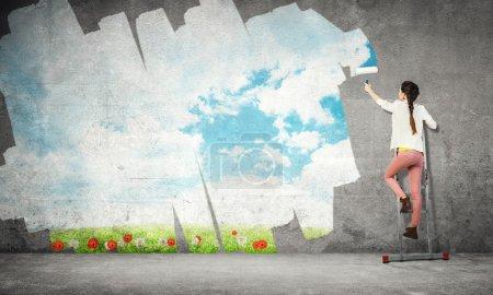 Foto de Mujer joven de pie en escalera y pared de pintura - Imagen libre de derechos