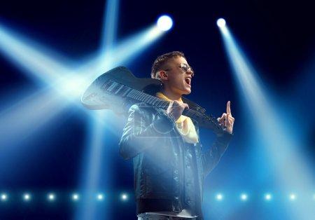 Photo pour Jeune homme musicien rock dans les lumières de la scène. Rock star sur scène - image libre de droit
