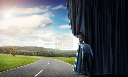 Homme d'affaires ouvrant rideau de velours