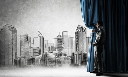 Photo for Young businessman presenting construction project behind curtain - Royalty Free Image