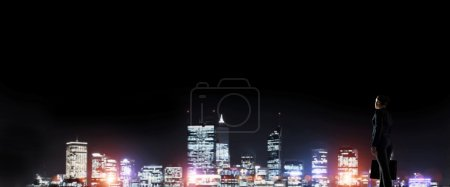 Businesswoman looking at night glowing city