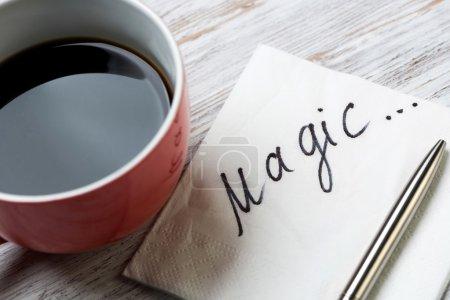Photo pour Tasse de café et serviette avec message sur table en bois. Message romantique écrit sur une serviette. Magie - image libre de droit