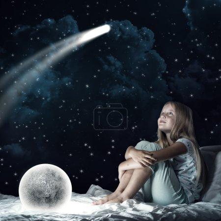 Photo pour Jolie fille assise au lit et regardant la planète lune - image libre de droit