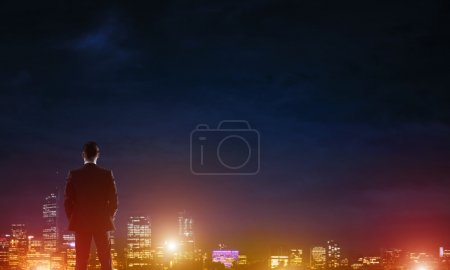 Businessman viewing night glowing city