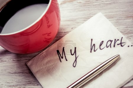 Photo for Cup of coffee and napkin with message on wooden table. Romantic message written on napkin. My heart - Royalty Free Image