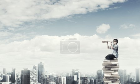 Photo for Kid of school age sitting on pile of books and looking in spyglass - Royalty Free Image