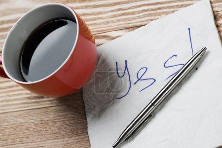 Photo pour Tasse de café et serviette avec message sur table en bois. Message romantique écrit sur une serviette. Oui. - image libre de droit