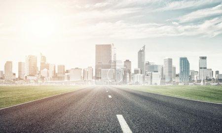 Photo pour Paysage naturel avec la route asphaltée et ville moderne - image libre de droit