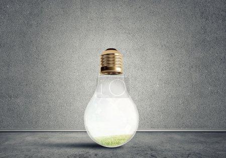 Foto de Bombilla de cristal en habitación vacía de hormigón. Concepto ecológico - Imagen libre de derechos