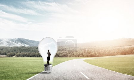 Photo for Young businesswoman trapped inside of light bulb on asphalt road - Royalty Free Image