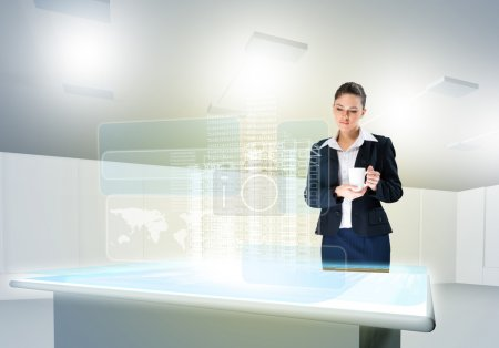 Photo for Businesswoman looking at hologram of construction project - Royalty Free Image