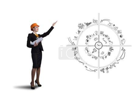 Photo pour Jeune femme ingénieur en hardhat avec des papiers à la main - image libre de droit