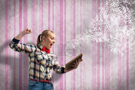 Photo pour Jeune femme excitée dans casual avec livre dans les mains - image libre de droit