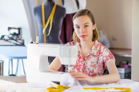 Photo for Young attractive needlewoman at studio working with sewing machine - Royalty Free Image