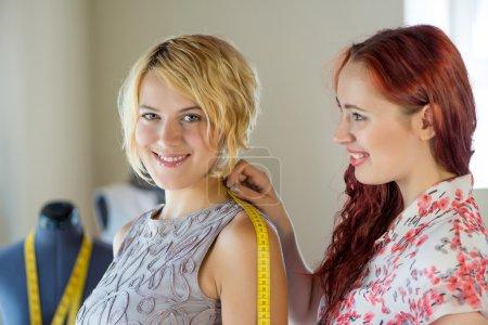 Photo pour Jeune femme à l'aiguille prenant des mesures du client féminin - image libre de droit