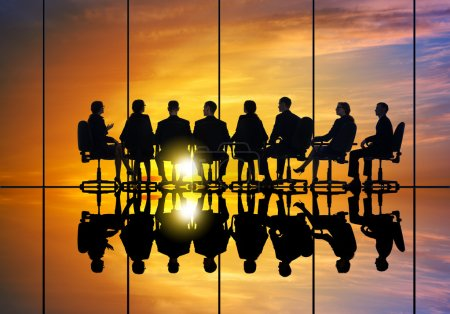 Photo for Silhouettes of group of business people against sunset - Business meeting - Royalty Free Image