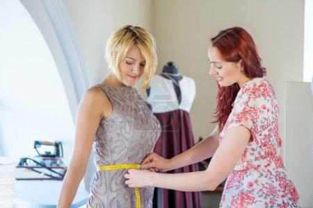 Photo pour Jeune femme à l'aiguille prenant des mesures de la cliente - Dresseuse au travail - image libre de droit