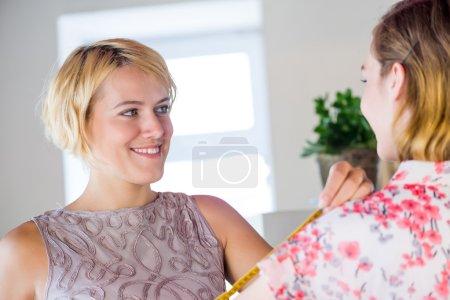 Photo pour Jeune femme à l'aiguille blonde prenant des mesures de client - Dressmaker au travail - image libre de droit