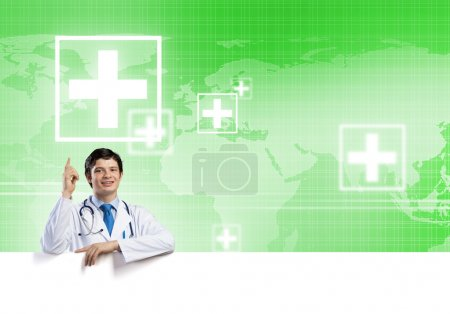 Photo pour Jeune beau docteur tenant une bannière blanche. Placez votre texte - image libre de droit