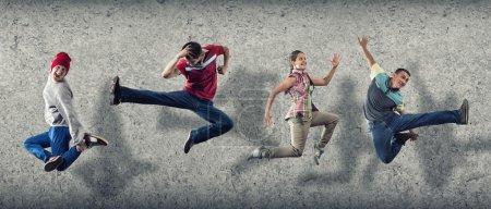 Photo pour Groupe de danseurs en saut sur fond de ciment - image libre de droit