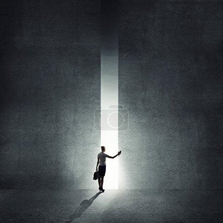 Photo pour Vue arrière de la femme d'affaires permanent à la lumière de façon - image libre de droit
