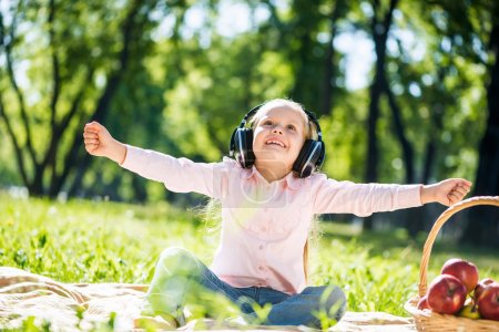 Photo for Little cute girl in summer park listening music - Royalty Free Image