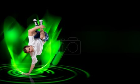 Photo for Young breakdancer performing a hand stand on color background - Royalty Free Image