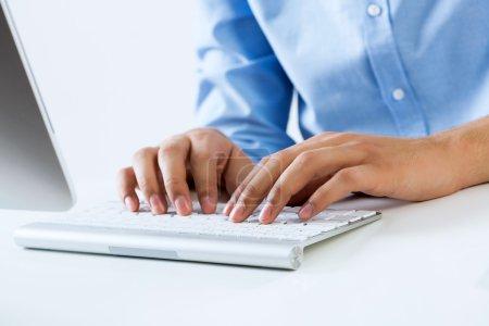Photo pour Jeune homme au travail assis au bureau et tapant sur le clavier - image libre de droit