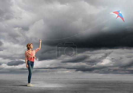 Photo pour Adolescente en jeans jouant avec cerf-volant - image libre de droit