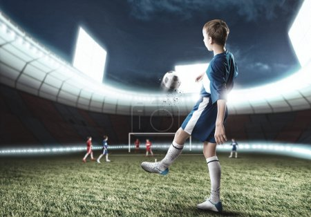 Photo for Excited boy football player at stadium kicking ball - Royalty Free Image