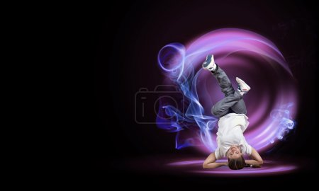 Photo for Young woman hip hop dancer with fire effect at background - Royalty Free Image