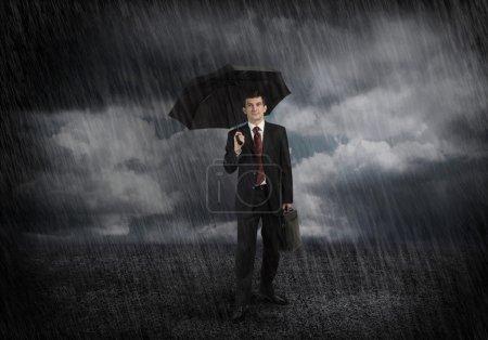 Photo pour Jeune homme d'affaires en costume noir avec parapluie - image libre de droit