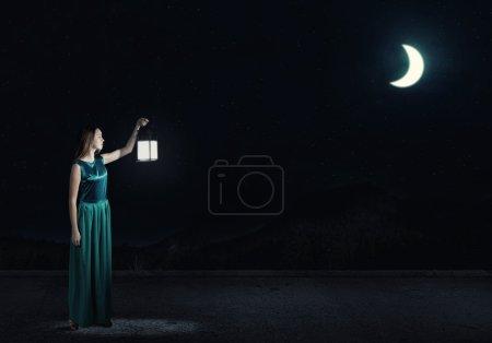 Photo pour Jeune femme attrayante en robe verte avec lanterne marchant dans l'obscurité - image libre de droit