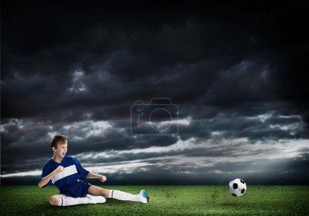 Photo for Kid boy kicking soccer ball at stadium field - Royalty Free Image