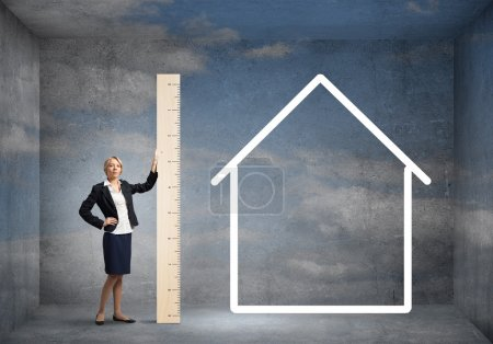 Young businesswoman measuring house