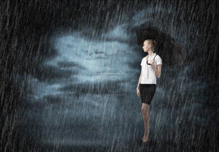 Photo pour Jeune femme d'affaires avec parapluie debout sous la pluie - image libre de droit