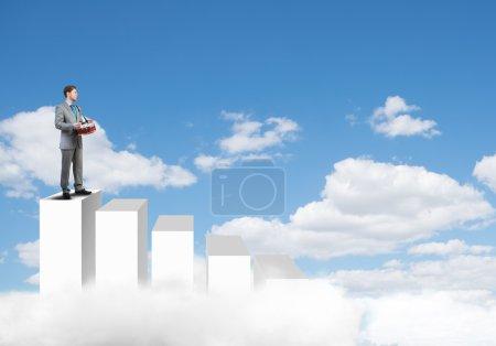 Photo pour Jeune homme d'affaires debout sur des barres graphiques et jouant de la batterie - image libre de droit