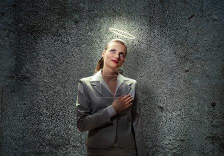 Photo pour Jeune femme d'affaires sainte avec la lumière au-dessus de sa tête - image libre de droit