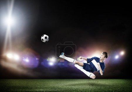 Kid boy kicking soccer ball
