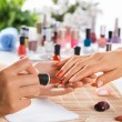 Woman in salon receiving manicure by nail beautici...