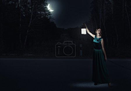 woman in green dress with lantern