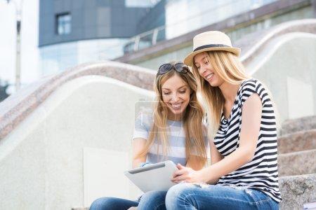 Photo pour Deux jeunes amies assis sur les marches et utilisant la tablette pc - image libre de droit