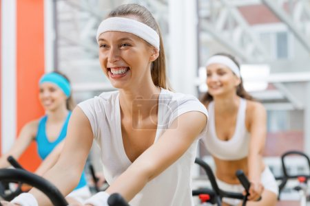 Photo for Small group of young people exercising on bikes in fitness center - Royalty Free Image