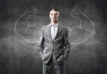 Photo for Businessman with strong arms drawn with chalk behind his back - Royalty Free Image