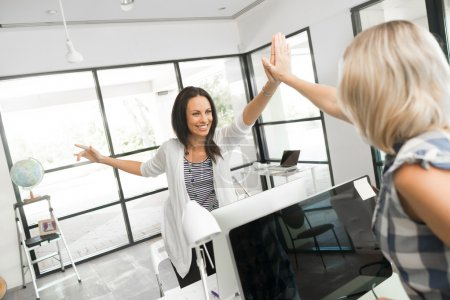 women in office giving high five